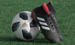 Balón junto a botas Adidas